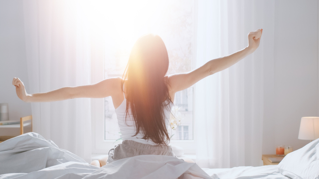 朝日を浴びながら起きる女性