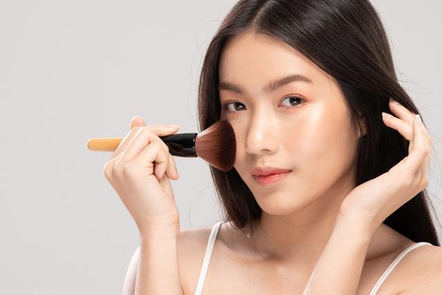 ブラシでチークを塗る韓国女性